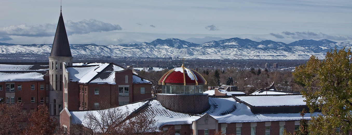 Photo of campus skyline with snow-covered roofs.